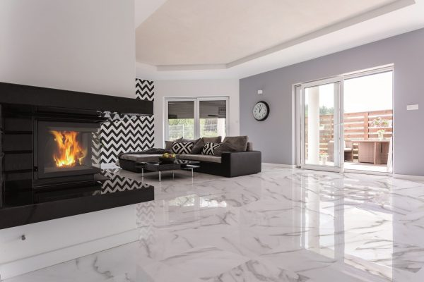 White and spacious modern living room with fireplace and large sofa